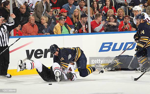 Tim Connolly of the Buffalo Sabres jumps onto Niklas Hjalmarsson of the Chicago Blackhawks after his Buffalo teammate Jason Pominville was injured at...