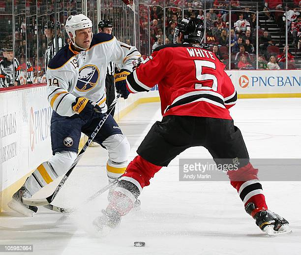 Tim Connolly of the Buffalo Sabres passes the puck into the zone while being defended by Colin White of the New Jersey Devils during the game at the...