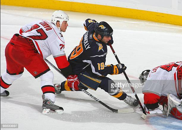 Tim Connolly of the Buffalo Sabres skates to the net for the rebound as Joe Corvo of the Carolina Hurricanes helps defend the play during their NHL...