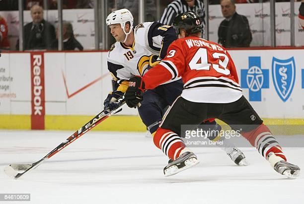 Tim Connolly of the Buffalo Sabres skates with the puck against James Wisniewski of the Chicago Blackhawks during the game on January 14 2009 at the...