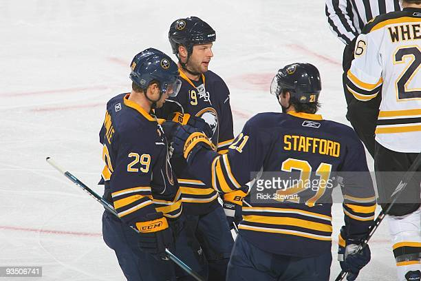 Tim Connolly of the Buffalo Sabres talks with teammates Drew Stafford and Jason Pominville during the game against the Boston Bruins at HSBC Arena on...