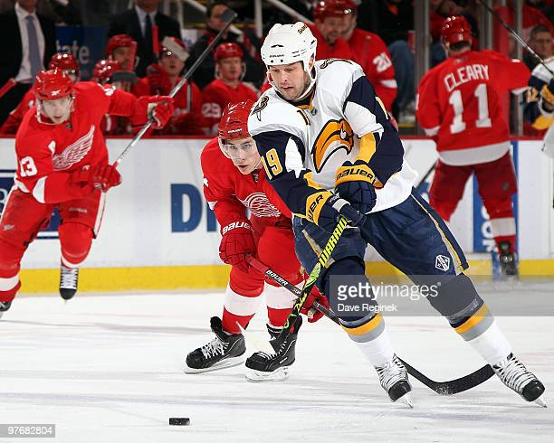 Tim Connolly of the Buffalo Sabres tries to keep control of the puck away from Valtteri Filppula of the Detroit Red Wings during an NHL game at Joe...