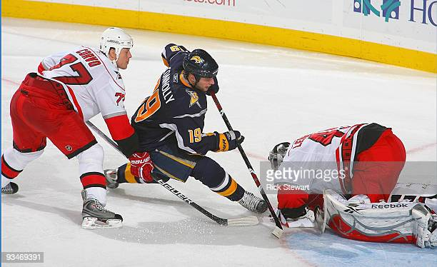 Tim Connolly of the Buffalo Sabres tries to stuff the puck past Michael Leighton of the Carolina Hurricanes as Joe Corvo of the Hurricanes defends as...