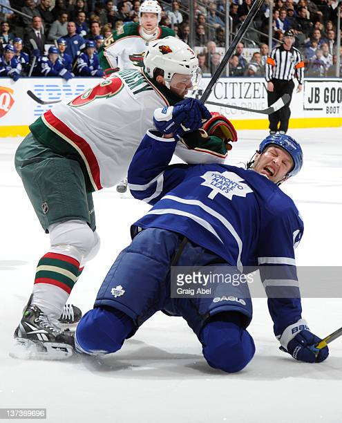 Tim Connolly of the Toronto Maple Leafs is checked to the ice by Marek Zidlicky of the Minnesota Wild during NHL game action January 19 2012 at Air...