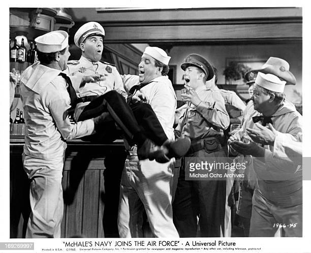 Tim Conway is hoisted onto an Australian bar by his newly-found 'comrades' in a scene from the film 'McHale's Navy Joins The Air Force', 1965.
