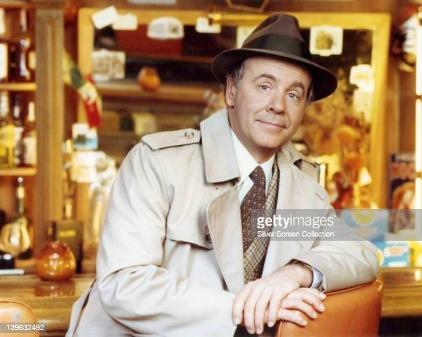 Tim Conway, US actor and comedian, wearing a beige overcoat over a tweed jacket, a white shirt and brown tie, with a brown fedora with a black band,...