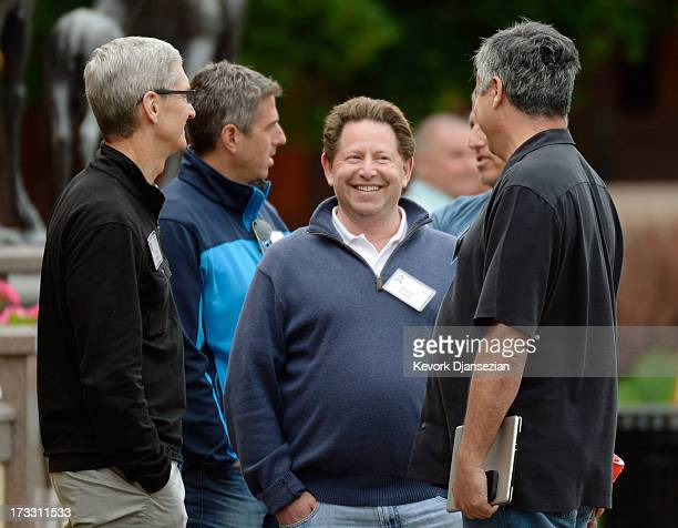 Tim Cook and senior vice president of Internet Software and Services Eddy Cue of Apple speak with CEO of Activision Blizzard Bobby Kotick , and...