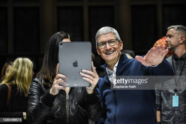 Tim Cook CEO of Apple laughs while Lana Del Rey takes a photo during a launch event at the Brooklyn Academy of Music on October 30 2018 in New York...
