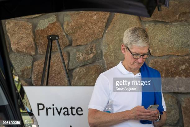 Tim Cook chief executive officer of Apple checks his iPhone during the annual Allen Company Sun Valley Conference July 13 2018 in Sun Valley Idaho...