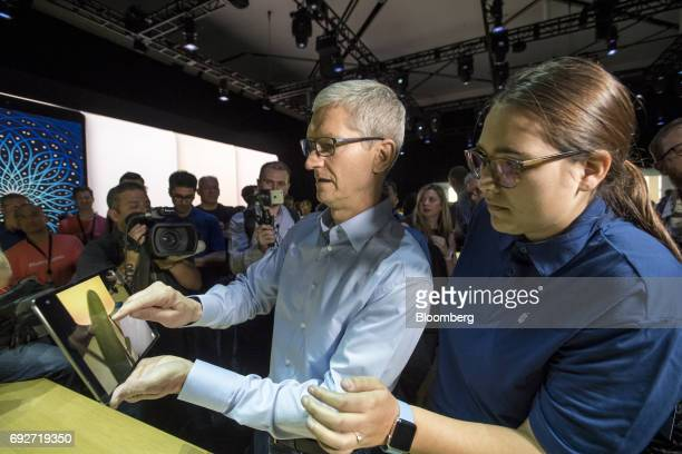 Tim Cook chief executive officer of Apple Inc center left uses an iPad Pro during the Apple Worldwide Developers Conference in San Jose California US...