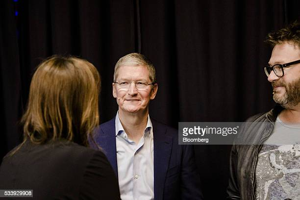 Tim Cook chief executive officer of Apple Inc center speaks with Gillian Tans chief executive officer of Bookingcom left and Steven Schuurman chief...
