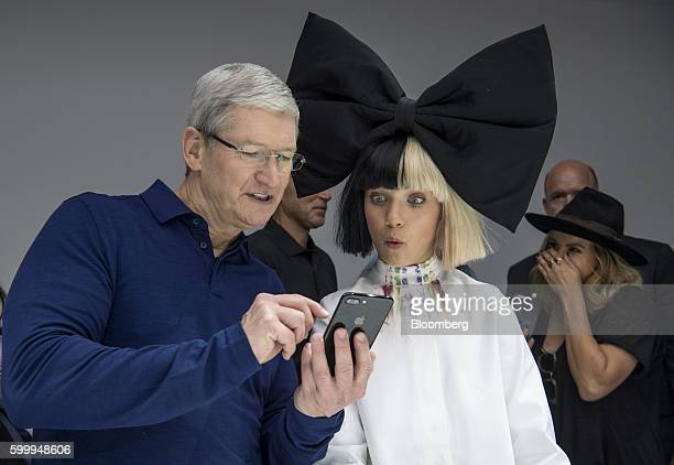 Tim Cook chief executive officer of Apple Inc left holds an iPhone 7 Plus while speaking with dancer Maddie Ziegler during an event in San Francisco...