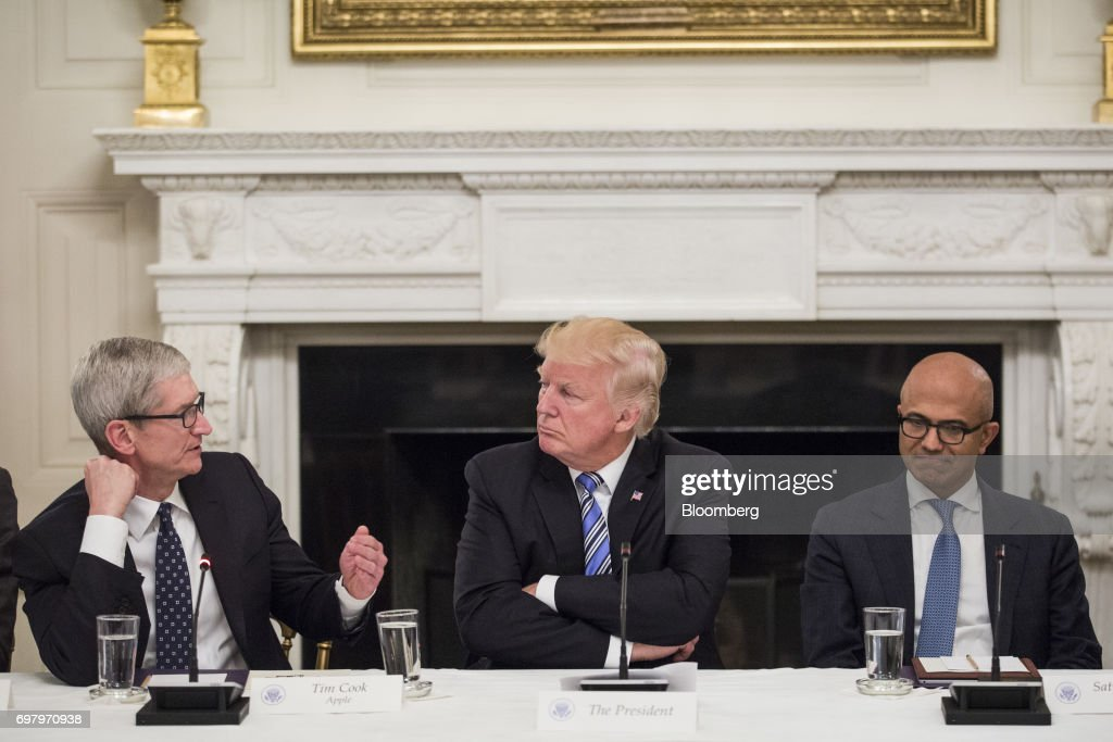 Tim Cook, chief executive officer of Apple Inc., left, speaks as U.S. President Donald Trump, center, and Satya Nadella, chief executive officer of Microsoft Corp., listen during the American Technology Council roundtable hosted at the White House in Washington, D.C., U.S., on Monday, June 19, 2017. Executives from many of the world's largest technology companies gathered for the first meeting of the American Technology Council with Trumpand his senior advisers. Photographer: Zach Gibson/Bloomberg via Getty Images