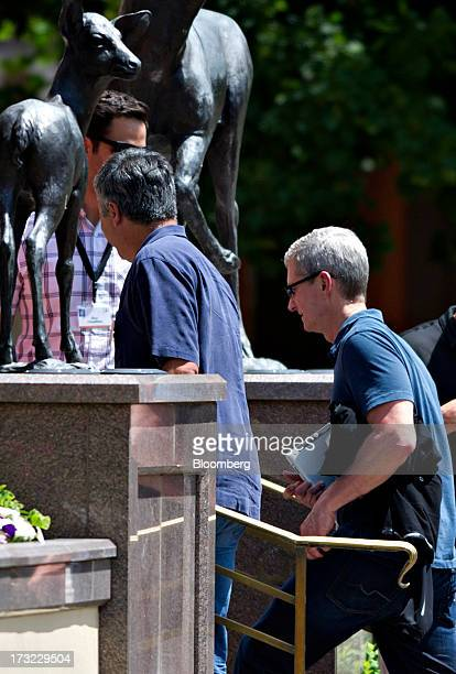 Tim Cook chief executive officer of Apple Inc right and Eddy Cue senior vice president of internet software and services at Apple Inc center walk...
