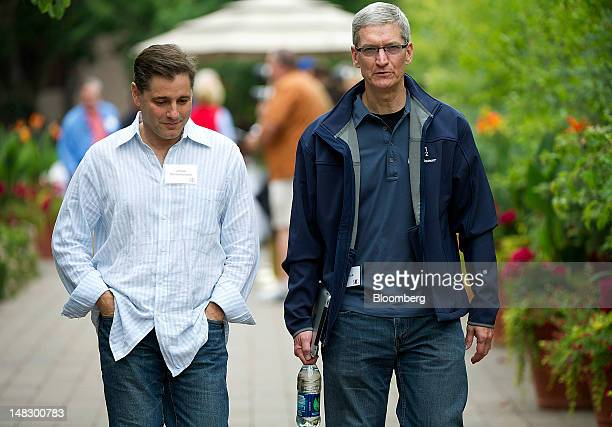 Tim Cook chief executive officer of Apple Inc right and Julius Genachowski chairman of the US Federal Communications Commission talk while leaving a...