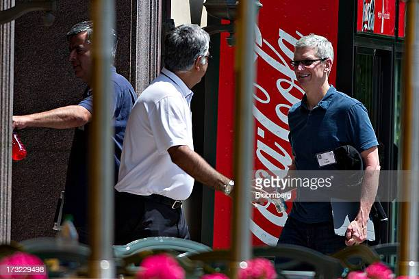 Tim Cook, chief executive officer of Apple Inc., right, follows Eddy Cue, senior vice president of internet software and services at Apple Inc.,...