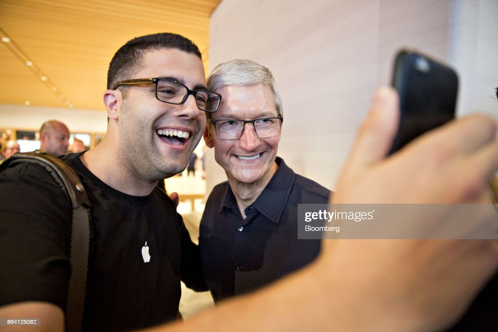 Tim Cook, chief executive officer of Apple, Inc., right, poses for a selfie photograph with a customer during the opening of the new Apple Michigan Avenue store in Chicago, Illinois, U.S., on Friday, Oct. 20, 2017. The building features exterior walls made entirely of glass with four interior columns supporting a 111-by-98 foot carbon-fiber roof, designed to minimize the boundary between the city and the Chicago River. Photographer: Daniel Acker/Bloomberg via Getty Images
