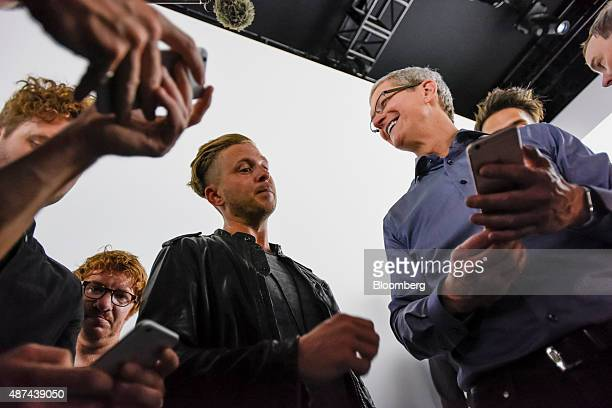 Tim Cook chief executive officer of Apple Inc right speaks with Ryan Tedder lead singer of One Republic as other members of the band look on after a...