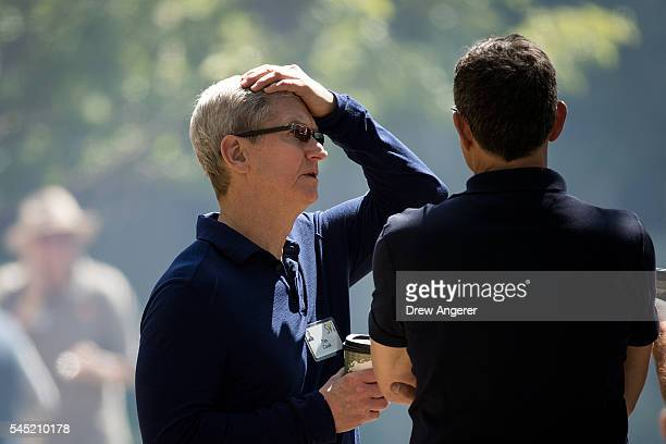 Tim Cook chief executive officer of Apple Inc speaks with Bob Iger chief executive officer of The Walt Disney Company as they attend the annual Allen...