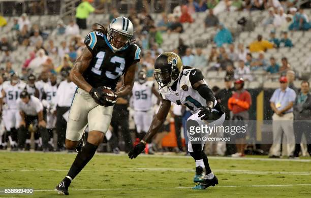 Tim Cook of the Jacksonville Jaguars attempts to tackle Kelvin Benjamin of the Carolina Panthers during a preseason game at EverBank Field on August...