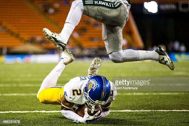 Tim Crawley of the San Jose State Spartans dives into the end zone for a touchdown against the Hawaii Warriors as Daniel Lewis Jr #15 of the Hawaii...