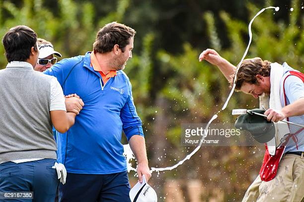 Tim Duffy sprays champagne on Jim Renner and his caddie after Renner's three stroke victory on the 18th hole green of the Crooked Cat Course during...