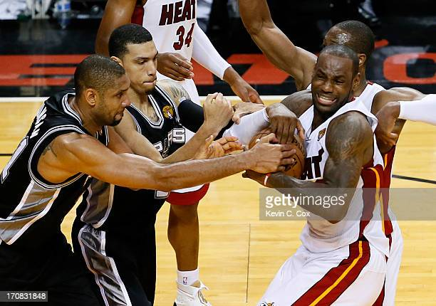 Tim Duncan and Danny Green of the San Antonio Spurs battle for the ball against LeBron James and Dwyane Wade of the Miami Heat in overtime during...