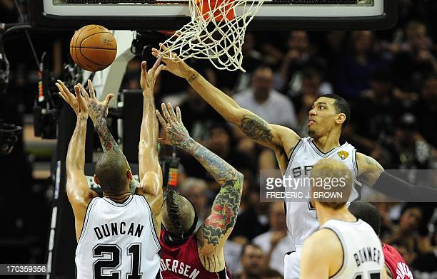 Tim Duncan and Danny Green of the San Antonio Spurs vie for the ball beneath the basket with Chris Andersen of the Miami Heat during game 3 of the...