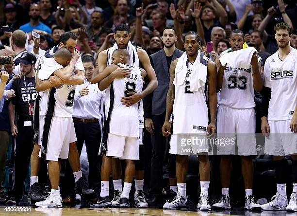 Tim Duncan celebrates with Patty Mills of the San Antonio Spurs in the closing minutes of Game Five of the 2014 NBA Finals against the Miami Heat at...