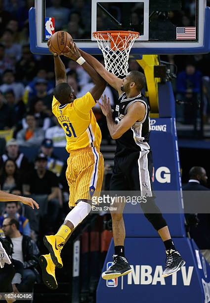 Tim Duncan of the San Antonio Spurs blocks a shot by Festus Ezeli of the Golden State Warriors at Oracle Arena on February 22 2013 in Oakland...