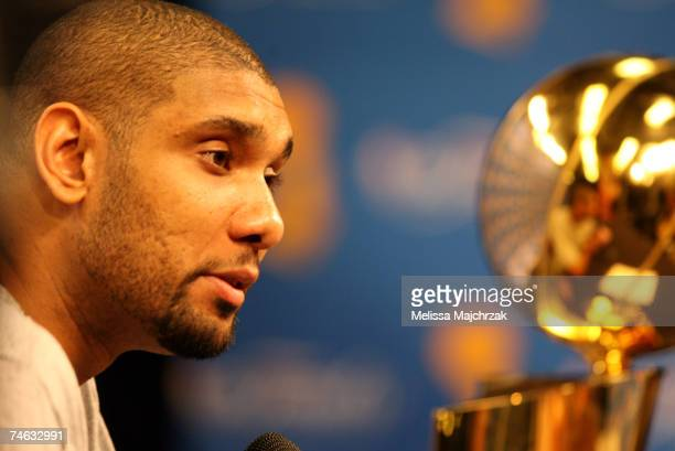 Tim Duncan of the San Antonio Spurs brings the Larry O'Brien Championship Trophy to the postgame press conference after defeating the Cleveland...