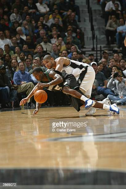 Tim Duncan of the San Antonio Spurs dives fo the ball with Anthony Goldwire of the Minnesota Timberwolves January 14 2004 at the SBC Center in San...