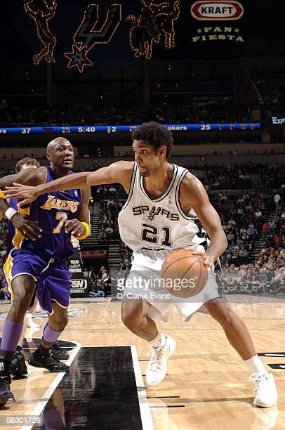 Tim Duncan of the San Antonio Spurs drives past Lamar Odom of the Los Angeles Lakers on November 29 2005 at the SBC Center in San Antonio Texas NOTE...