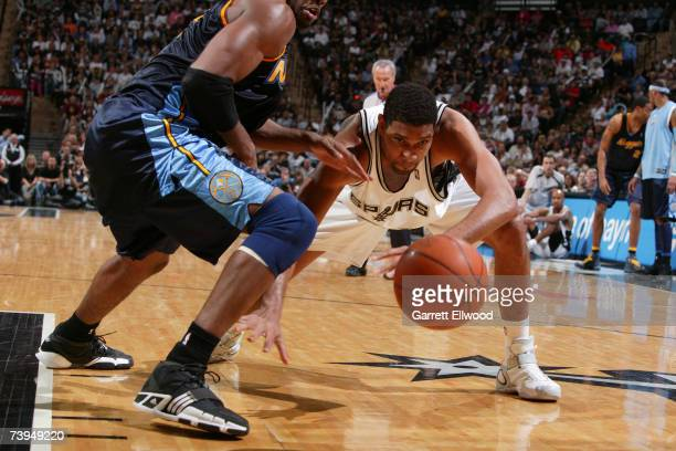 Tim Duncan of the San Antonio Spurs fights for a loose ball against Nene of the Denver Nuggets in Game One of the Western Conference Quarterfinals...