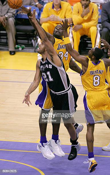 Tim Duncan of the San Antonio Spurs gets past Shaquille O'Neal and Kobe Bryant of the Los Angeles Lakers during Game six of the Western Conference...