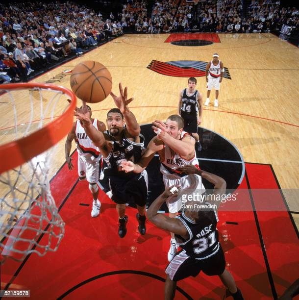 Tim Duncan of the San Antonio Spurs goes up for the rebound against Joel Przybilla of the Portland Trail Blazers at Rose Garden on January 24 2005 in...