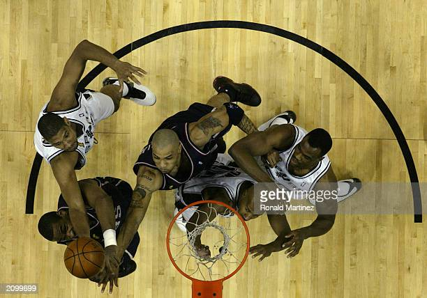 Tim Duncan of the San Antonio Spurs grabs a rebound over Jason Collins and Kenyon Martin of the New Jersey Nets in game six of the 2003 NBA Finals at...