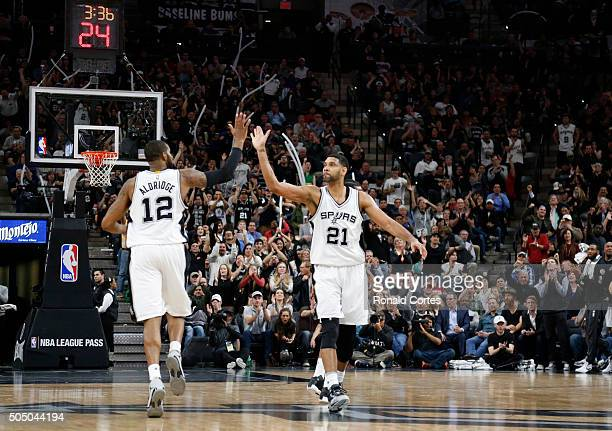Tim Duncan of the San Antonio Spurs high fives teammate LaMarcus Aldridge of the San Antonio Spurs after a basket at ATT Center on January 14 2016 in...