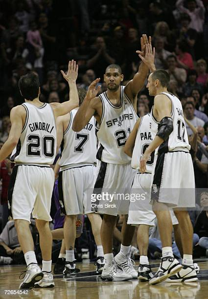 Tim Duncan of the San Antonio Spurs high fives teammates Manu Ginobili and Brent Barry during the game against the Phoenix Suns at ATT Center on...