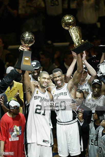 Tim Duncan of the San Antonio Spurs holds up his NBA Finals MVP award as teammate David Robinson holds up the 2003 NBA Championship trophy as the San...