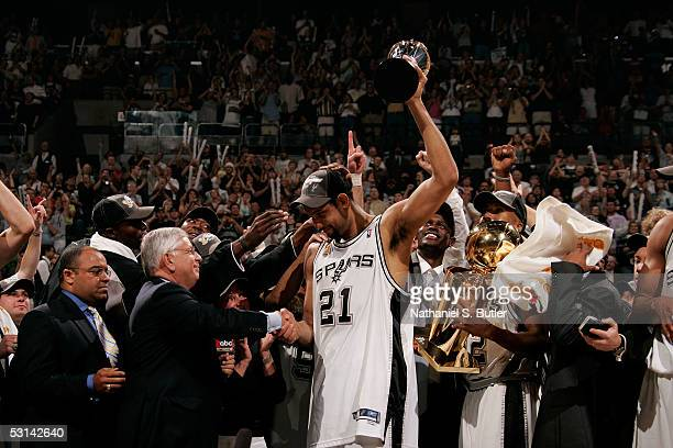 Tim Duncan of the San Antonio Spurs holds up the Finals MVP trophy as he shakes hands with NBA Commissioner David Stern following the Spurs 81-74 win...