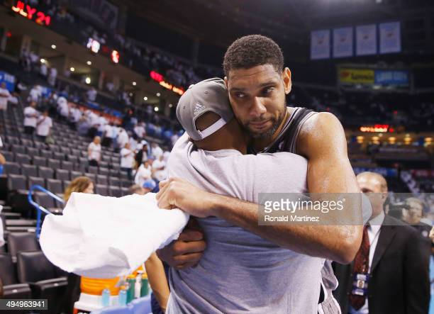 Tim Duncan of the San Antonio Spurs hugs teammate Patty Mills after the Spurs defeated the Oklahoma City Thunder 112107 in overtime during Game Six...