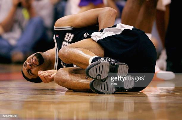 Tim Duncan of the San Antonio Spurs lays on the ground after being kicked in the groin in the game against the Phoenix Suns in Game five of the...