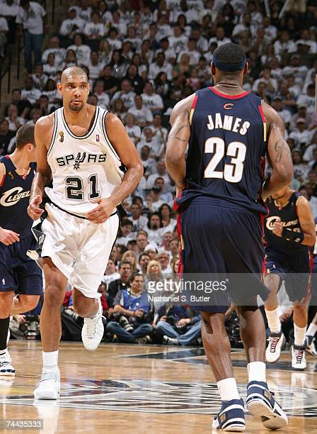 Tim Duncan of the San Antonio Spurs looks at LeBron James of the Cleveland Cavaliers as he runs up court in Game One of the NBA Finals at the AT&T...