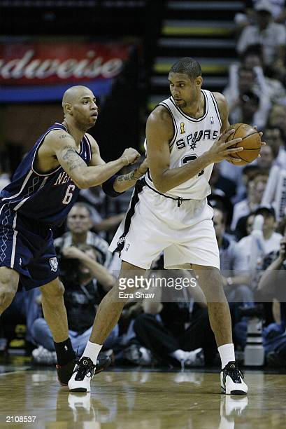 Tim Duncan of the San Antonio Spurs looks for an opening around Kenyon Martin of the New Jersey Nets in game six of the 2003 NBA Finals on June 15...