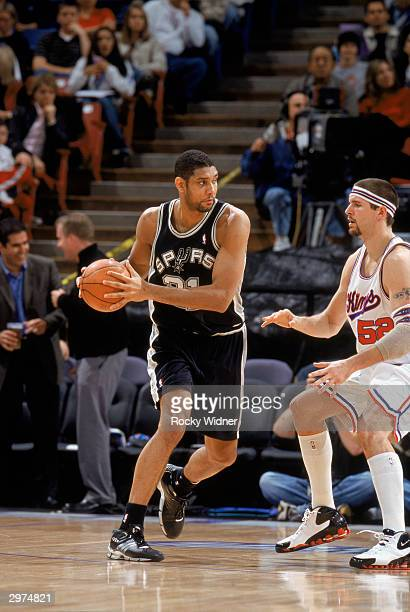 Tim Duncan of the San Antonio Spurs looks to make the pass against Brad Miller and of the Sacramento Kings during the NBA game at Arco Arena on...