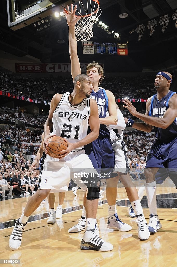 Tim Duncan #21 of the San Antonio Spurs moves the ball against Dirk Nowitzki #41 and Erick Dampier #25 of the Dallas Mavericks in Game One of the Western Conference Quarterfinals during the 2009 NBA Playoffs at AT&T Center on April 18, 2009 in San Antonio, Texas. The Mavericks won 105-97.