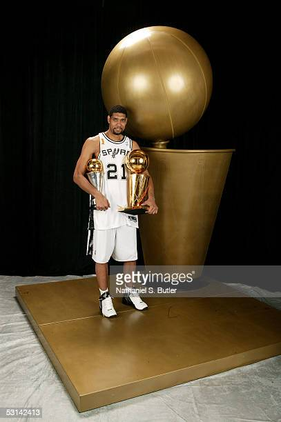 Tim Duncan of the San Antonio Spurs poses for a portrait with the Larry O'Brien Championship trophy and his 2005 Finals MVP trophy following Game...