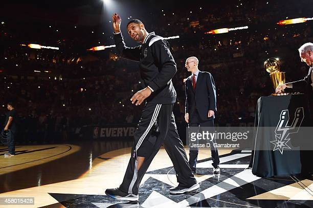 Tim Duncan of the San Antonio Spurs raises his championship ring that he received from NBA Commissioner Adam Silver and owner Peter Holt during the...