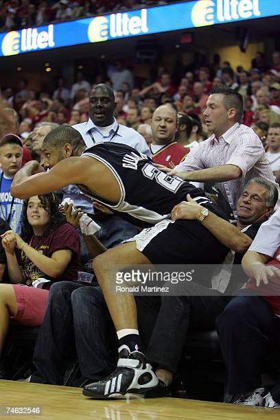 Tim Duncan of the San Antonio Spurs saves the ball and falls into the lap of a fan in the fourth quarter against the Cleveland Cavaliers in Game Four...